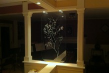 Dual surface, etched tree branch on one-inch thick glass. Used here as decorative accent, room divider.
