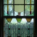 Leaded glass panels with cast rondels. These inserts fit in the interior openings of the double hung wood sash and grant privacy to a guest bathroom.
