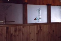 """Three laminated safety glass panels for a room divider in a local Cape Cod restaurant. These are examples of a """"negative blast,"""" where the designs are left clear and the remainder of the glass is frosted."""