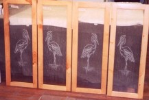 Etched herons compliment the antique seedy glass in these cabinets.